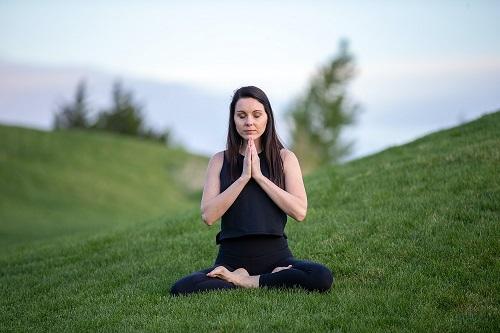 mujer practicando yoga sobre un césped bien cortado